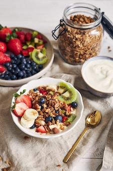 Чаши гранолы с йогуртом, фруктами и ягодами на белой поверхности