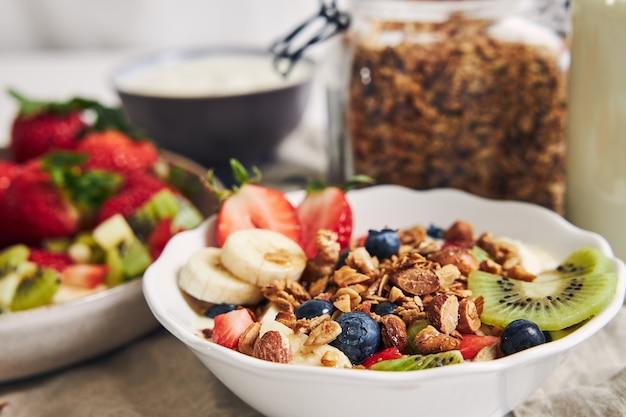 Миски мюсли с йогуртом, фруктами и ягодами на белой поверхности