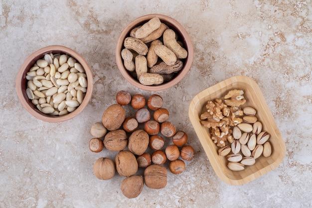 Чаши с фундуком, арахисом, семенами подсолнечника и попкорном на мраморной поверхности