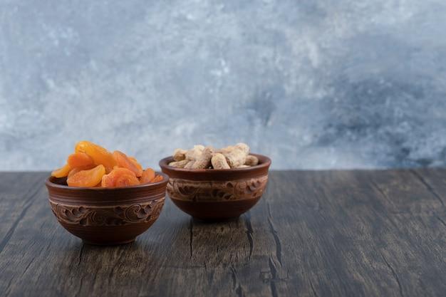 Чаши здоровых сушеных плодов абрикоса и арахиса в раковине на деревянном столе.