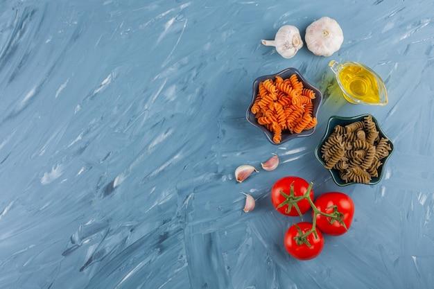 Чаши разноцветных сырых спиральных макарон со свежими красными помидорами и чесноком.