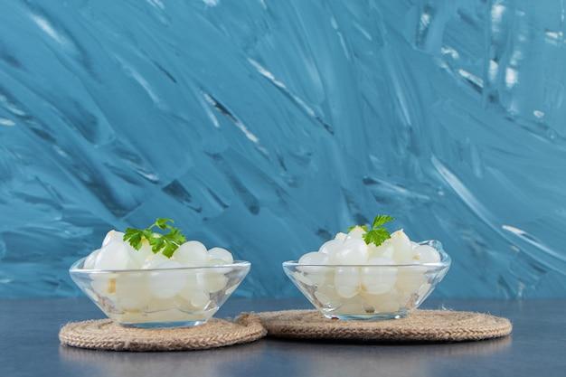 Чаши маринованного молодого лука на подставке на мраморной поверхности