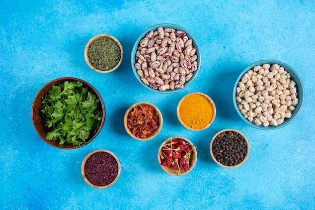 青の背景に生豆とスパイスのボウル。