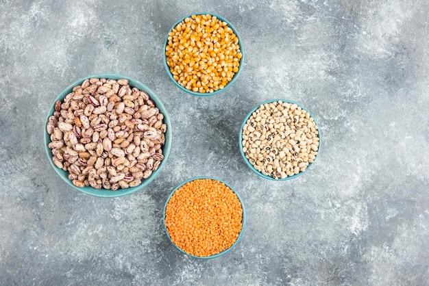대리석 표면에 원시 콩, 렌즈 콩 및 옥수수 그릇.
