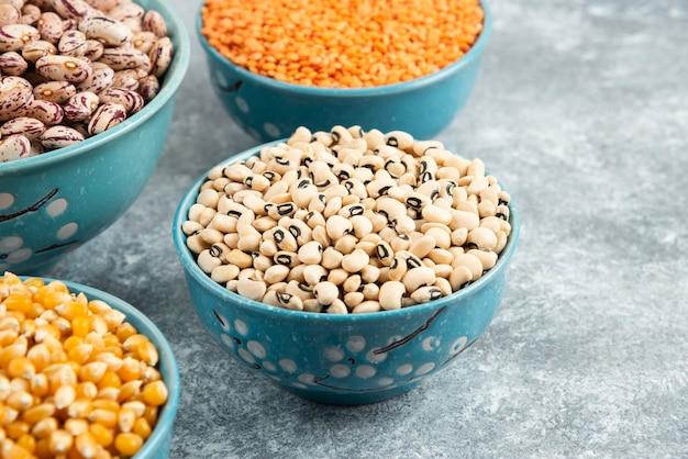 大理石の表面に生の豆、レンズ豆、トウモロコシの入ったボウル。