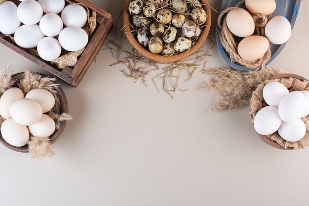 Миски сырых куриных и перепелиных яиц с мукой на бежевом столе.