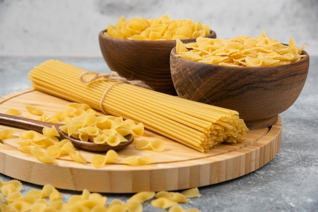 Чаши сырых сухих макарон и спагетти на мраморной поверхности.