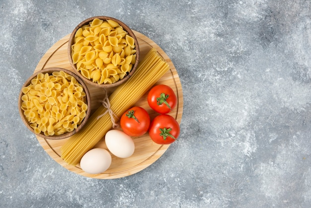 Чаши сырых макарон, яиц и свежих помидоров на мраморной поверхности.