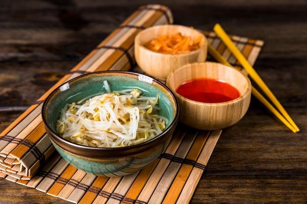 테이블 위에 플레이스 매트에 젓가락으로 콩나물과 레드 칠리 소스 그릇