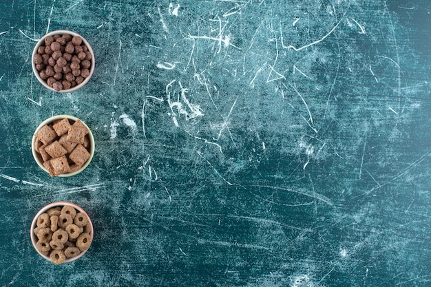 青いテーブルの上に、さまざまなシリアルのボウル。