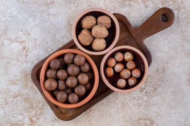 나무 판자에 다양한 견과류가 담긴 그릇