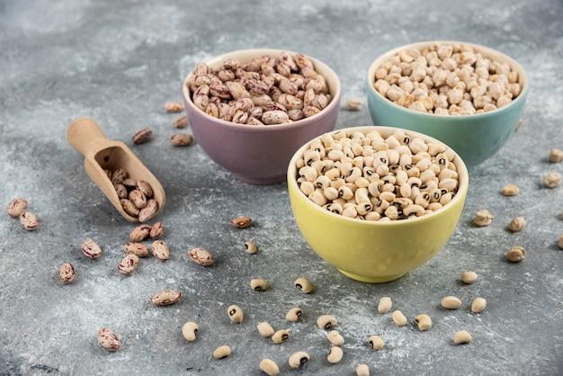 대리석 테이블 표면에 다양한 익히지 않은 콩이 담긴 그릇.