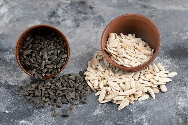 대리석 표면에 흩어져있는 흰색과 검은 색 해바라기 씨앗의 그릇