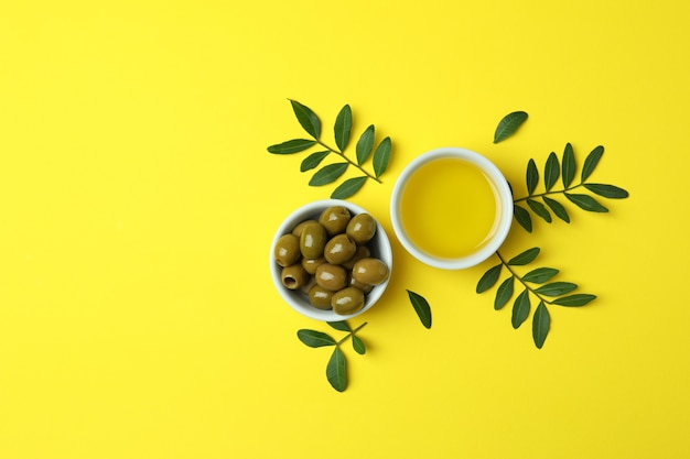 Bowls of oil and olives, and twigs on yellow surface
