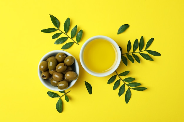 Bowls of oil and olives, and twigs on yellow