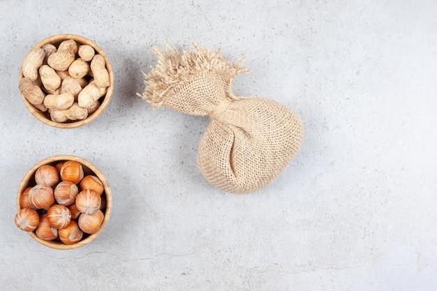 Ciotole di arachidi e nocciole accanto a un sacco su fondo di marmo. foto di alta qualità