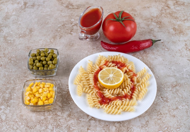 Bowls of peas and corn kernels next to plate of macaroni with a glass of ketchup and various vegetables on marble surface.
