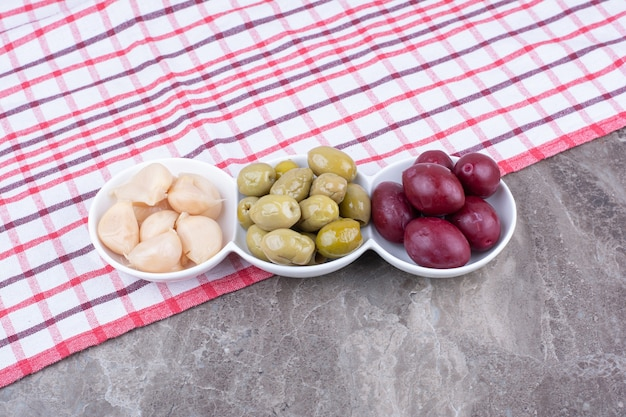 Bowls of pickled plums, olives and garlic on tablecloth.