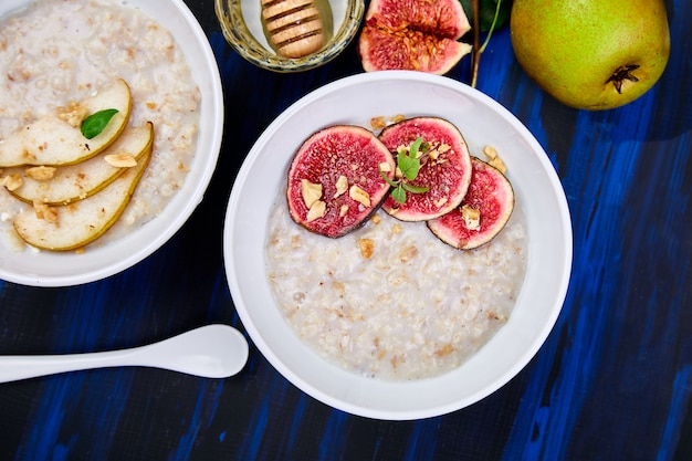 Bowls of porridge with pears slices and walnuts and porridge with figs