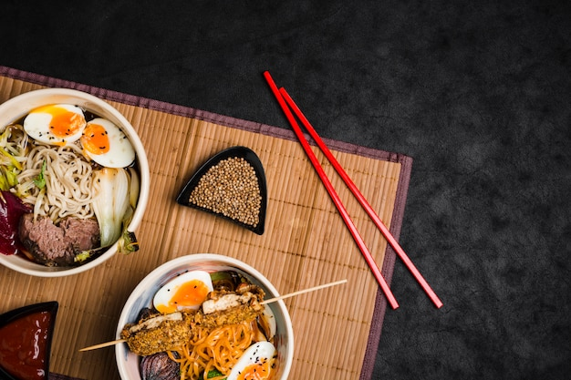 Bowls of ramen noodles with eggs and vegetables on chopsticks over the placemat against black background