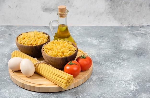 Ciotole di pasta cruda, uova, pomodori e olio d'oliva su superficie di marmo.