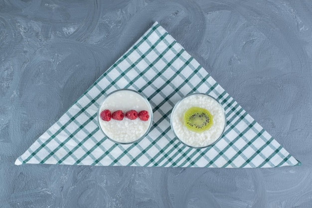 Bowls of rice pudding garnished with raspberries and kiwi slice on a tablecloth on marble table.