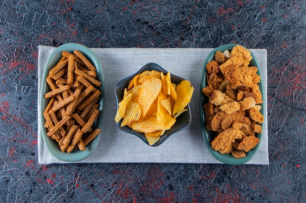 Bowls of tasty chips and crispy crackers on dark surface.