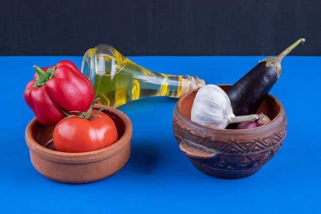 Ciotole di pomodoro, pepe e aglio con olio d'oliva su superficie blu