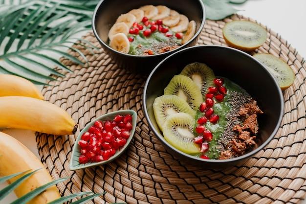 Bowls topped with kiwi, granola, garnet, chia and avocado