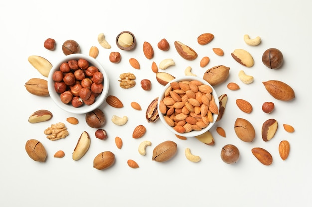 Bowls with almond and hazelnut, and different nuts on white background