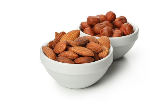 Bowls with almonds and hazelnuts on white