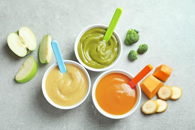 Миски с детским питанием на сером фоне
