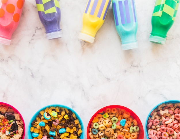 Bowls with cereals and bottles on table