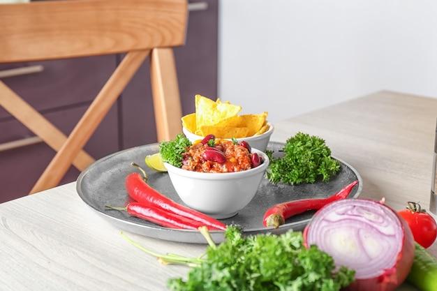 금속 트레이에 칠리 콘 카르네와 나초 칩이 담긴 그릇