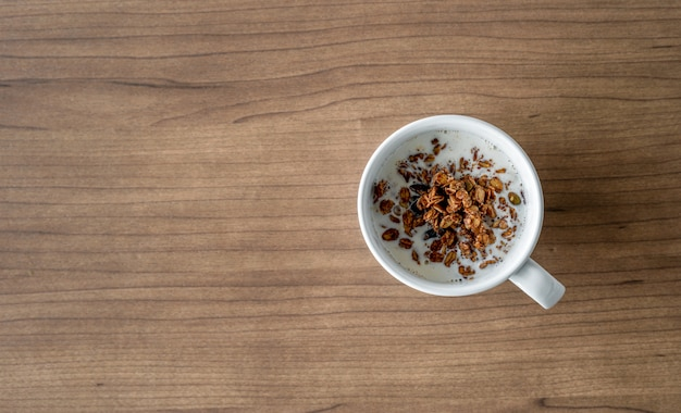 Bowls with chocolate cornflakes and milk for breakfast on wooden table. top view