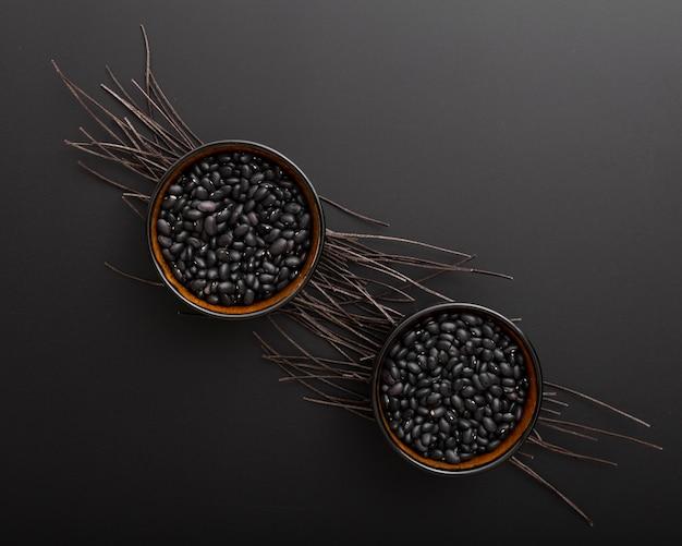 Bowls with dark beans on a dark background