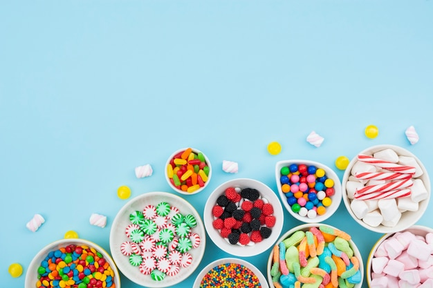 Bowls with delicious candies on table