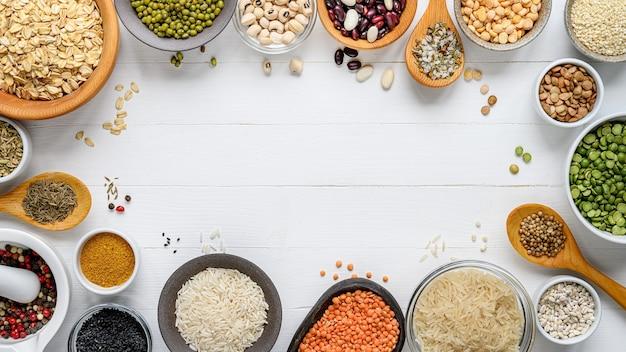 さまざまなシリアルのボウル:白い木製のテーブルにご飯、エンドウ豆、レンズ豆、豆、スパイス。フラットレイ。上面図。スペースをコピーします。