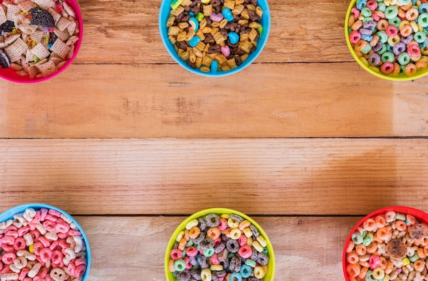 Bowls with different cereals on wooden table