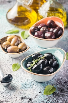 Bowls with different kind of olives green olives black olives kalamata olives with olive oil