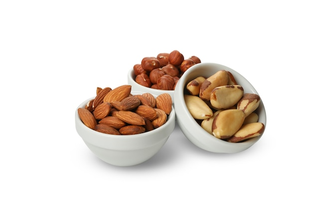 Bowls with different nuts isolated on white background