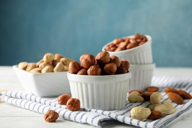 Чаши с разными орехами на белом деревянном фоне. витаминная пища