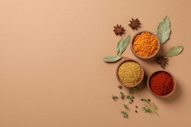 Bowls with different powder spices on craft background, space for text