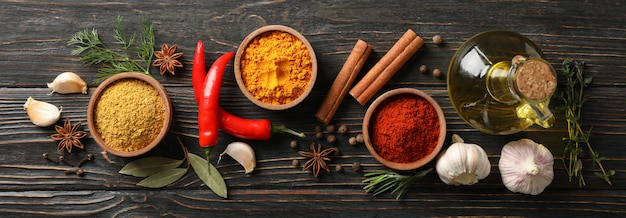 Bowls with different spices and ingredients on wooden background, space for text