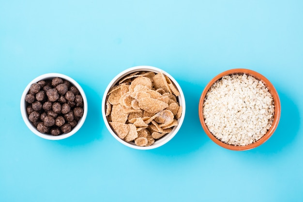 さまざまな種類の朝食が入ったボウル:水色のテーブルにオートミール、シリアル、チョコレートボール。上面図