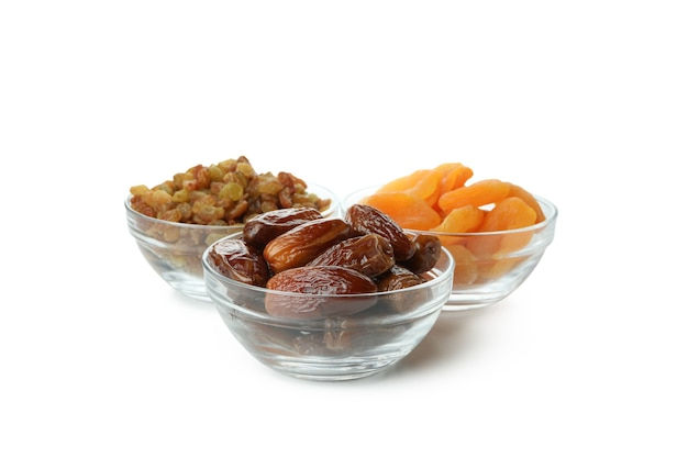 Bowls with dried dates, raisins and apricots isolated on white