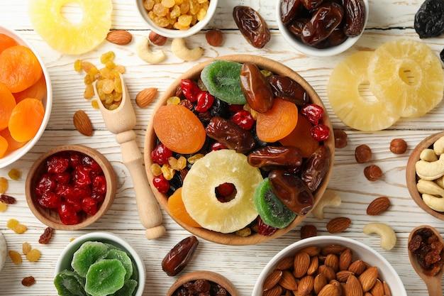ドライフルーツとナッツの白い木製のテーブルのボウル