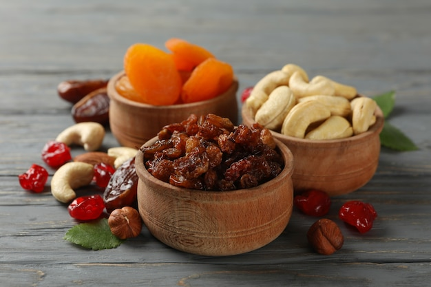 Bowls with dried fruits and nuts on gray wooden table