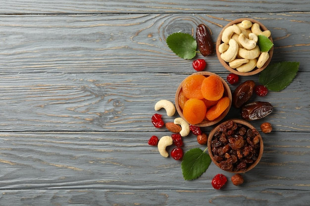 Bowls with dried fruits and nuts on gray wooden