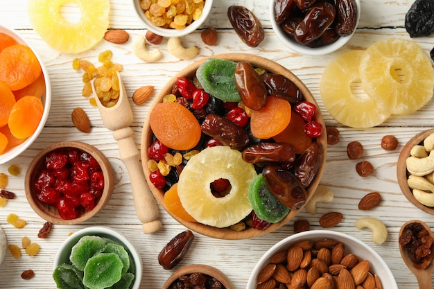 Bowls with dried fruits and nuts on white wooden table